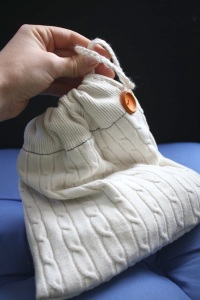 photograph of hand holding drawstring knitting bag